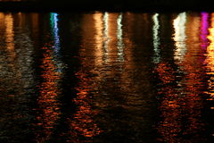 Reflections in the lagoon. The lights of village are reflected in the water of the lagoon. Small waves are illuminated by different colors Royalty Free Stock Photo