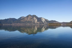 Reflections in the lake. Clear blue morning at lake Walchensee in Bavaria Stock Image