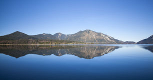 Reflections in the lake. Clear blue morning at lake Walchensee in Bavaria Royalty Free Stock Photo