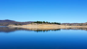 Reflections in Lake Jindabyne. Still water and lake reflections in landscape view on Lake Jindabyne, a popular travel, vacation and trout fishing destination of Stock Images