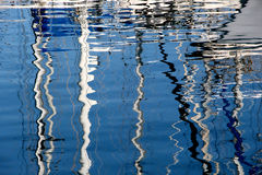 Reflections of the masts of some sailboats. The colorful reflections of the masts of some sailboats, landscape cut royalty free stock photos