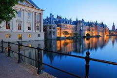 Reflections of the Mauritshuis and the Binnenhof 13 century gothic castle on the Hofvijver lake at dusk during the blue hour. With the clock tower of Grote of royalty free stock photography