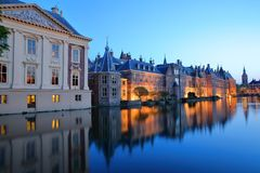 Reflections of the Mauritshuis and the Binnenhof 13 century gothic castle on the Hofvijver lake at dusk during the blue hour. With the clock tower of Grote of royalty free stock photo