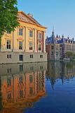 Reflections of the Mauritshuis and the Binnenhof 13 century gothic castle on the Hofvijver lake at sunset. The Hague, Netherlands royalty free stock photo