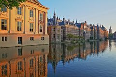Reflections of the Mauritshuis and the Binnenhof 13 century gothic castle on the Hofvijver lake at sunset. With the clock tower of Grote of Sint Jacobskerk on royalty free stock photo