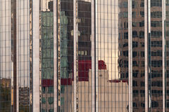Reflections in modern glass-walled building facade. Background of distorted reflections of a cityscape in a modern coporate glass-walled building facade royalty free stock image