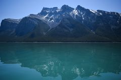 Reflections on a Mountain Lake. The sunlight brightly shimmers on the surface of Lake Minnewanka on a crystal clear spring day in 2017 near Banff, Alberta stock photography