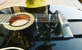 Reflections and music, symbols. Chrysanthemums reflected on the strings of a guitar, suggesting playing love songs and ballads Stock Images