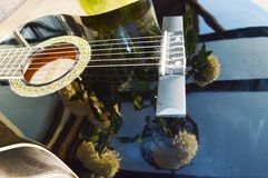 Reflections and musical notes, symbols. Chrysanthemums reflected on the strings of a guitar, suggesting playing love songs for the beloved persons Royalty Free Stock Image