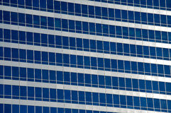 Reflections in office windows. Irregularly spaced windows on the side of an office building Royalty Free Stock Images