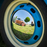 Reflections of an old car in the decorative wheel covers Stock Photos