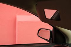 Reflections of a pink house in the mirrors inside a car royalty free stock images