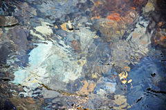 Reflections in a pool of water with colorful rocks and ripples. Royalty Free Stock Image
