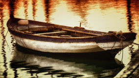 Reflections and ripples. A fishing boat in brown and green tones Royalty Free Stock Photo
