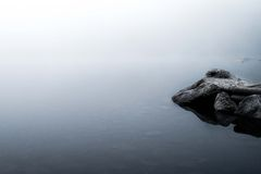 Reflections of rocks in a foggy lake Royalty Free Stock Photography