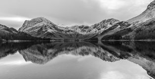 Reflections Of Snow On The Cumbrian Fells At Buttermere, Lake District, UK. Black and white landscape scene at Buttermere in the Lake District, UK. The Royalty Free Stock Photo