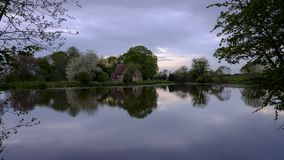 Reflections of St Leonard`s church in Hartley Mauditt Pond, South Downs National Park, UK stock photography