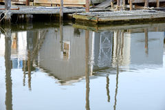 Reflections of a storage building at an old wharf and fishing do Stock Photography
