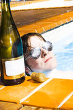 Reflections Of Success. Handsome young man with wet hair and sunglasses lounging up to his neck in the water of his sparkling pool alongside an open champagne Stock Photo