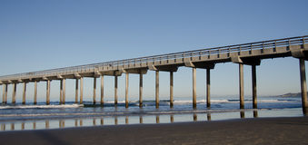 Reflections in sunrise under a tall Pier at La Jolla Bay Stock Image