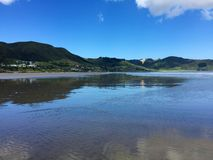 Reflections on surface of 90 Mile Beach, Ahipara, New Zealand Royalty Free Stock Images