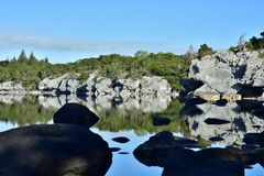 Country reflections on calm lake surface. Reflections on surface of Muckross Lake while large boulders near shore are in deep shadow stock images