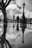 Reflections by the Thames. Silhouetted man, tree and Big Ben reflected in puddles by the Thames Stock Photos