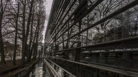 Reflections: treeline along a Munich channel mirrored in a building stock image
