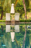 Reflections of umbrella at swimming pool in a tropical Stock Image
