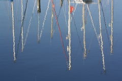 Yacht masts reflecting on the water. Masts from a group of yachts on a summer's day reflecting on the shimmering water Royalty Free Stock Image