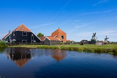 Reflections in the water of the farms and windmills on a lovely day, with a blue sky. Zaanse Schans. Holland royalty free stock images
