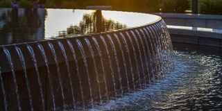 Reflections on the water of a fountain at sunset stock photography