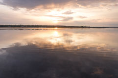Reflections in water at sunrise by the river. Smoke on the water at sunrise by the river at the end of summer Stock Image