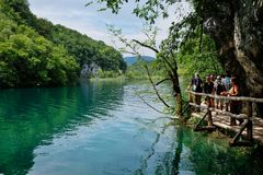 Reflections in Water and Wooden Bridge, Plitvice Lakes, Croatia. Reflections in calm water and visitors on walking track wooden bridge, Plitvice Lakes, Plitvice stock images
