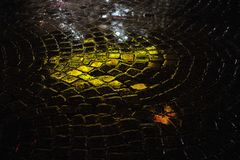 Reflections on Wet Cobblestone Street. Reflections from neon lights in green on wet, rainy street of cobblestone.  Closeup horizontal photo at night. Evening Royalty Free Stock Photo