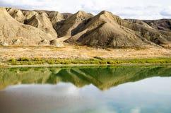 Reflective autumn river. Calm South Saskatchewan River in autumn reflecting the sky & desert like hills Royalty Free Stock Photo