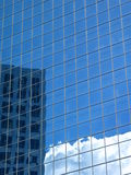 Reflective Building. Blue office building reflecting clouds and the building next door royalty free stock image