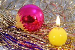 Reflective christmas tree toy. Reflective christmas tree toy and a candle on sparkly decorations stock photo