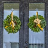 Reflective double glass door with wreaths in Utah. Reflective glass door with wreaths viewed on a snowy day in Daybreak, Utah. The holiday wreaths are stock photo