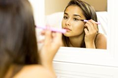 Mixed race young woman with brush eye liner on looking in the mi Stock Images