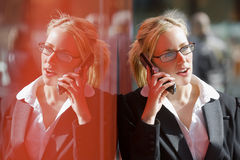Reflective Phone Call. A beautiful young female executive talking on her cell phone and reflected in the red wall of a hi-tech office building Royalty Free Stock Photo