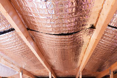 Reflective Radiant Heat Barriers Between Attic Joists Used as Ba. Insulating of attic with fiberglass cold barrier and reflective heat barrier used as baffle Stock Photos