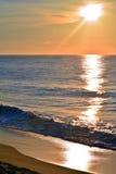 Reflective Seas Beneath A Golden Sunrise. The seas look reflective beneath a golden summer sunrise at the seashore Royalty Free Stock Image