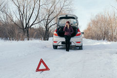 Reflective warning triangle before vehicle, an emergency situation on the road in winter, calls for help, woman talking. On cell phone, car broke down Royalty Free Stock Photo