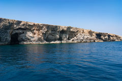 Reflective water of mediterranean sea. Diagonal perspective, rock, reflective calm vibrant water and clear sky. Malta, Summer 2015 Royalty Free Stock Photo