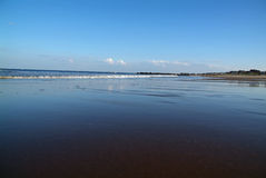Reflective water on ocean. Blue sky reflected in shallow water at ocean stock photography