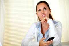 Reflective young woman looking up with cellphone Royalty Free Stock Images