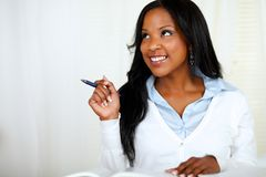 Reflective young woman smiling and studying Stock Photo