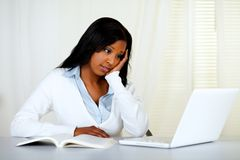 Reflective young woman studying on laptop Stock Photography