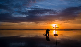 Reflecton Praying Man Cross. Wonderful reflection on a beach at sunset, with a man kneeling by it stock photography